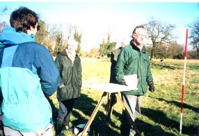 Steve Kemp helping the group to use the plane table. Long  shadows from the Winter sun made it clear where to put the measuring pole.